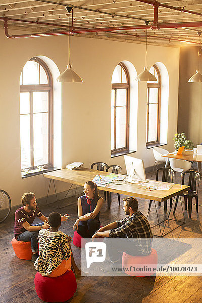 Kreative Geschäftsleute reden im Kreis im Büro