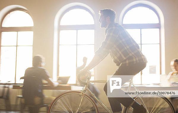 Lässiger Geschäftsmann auf dem Fahrrad im sonnigen Büro