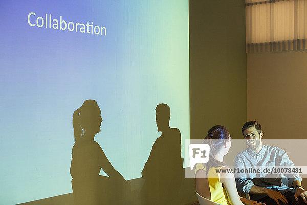 Geschäftsleute diskutieren über Zusammenarbeit in der audiovisuellen Präsentation