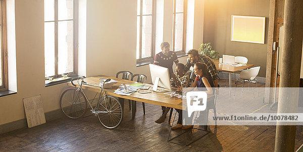 Lässige Geschäftsleute treffen sich rund um den Computer im Büro.