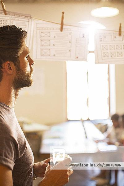 Nachdenklicher Geschäftsmann beim Durchsehen hängender Diagramme im Büro