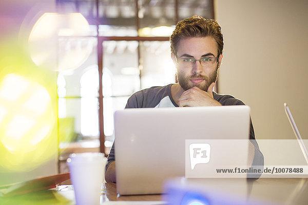 Fokussierter Gelegenheitsunternehmer bei der Arbeit am Laptop im Büro