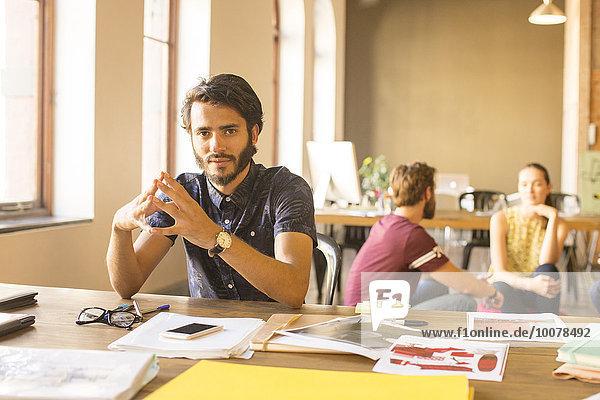 Porträt eines selbstbewussten  kreativen Geschäftsmannes  der mit Proofs im Büro arbeitet.