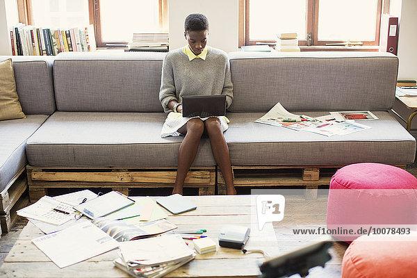 Kreative Geschäftsfrau beim Tippen auf digitalem Tablett auf Sofa im Büro