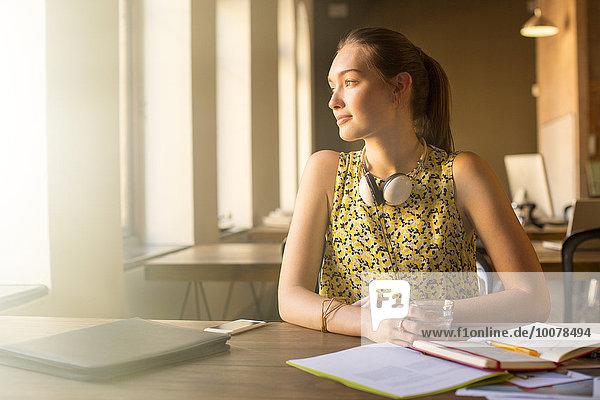 Nachdenkliche  lässige Geschäftsfrau mit Kopfhörer  die im Büro wegschaut