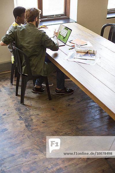 Geschäftsleute  die am Laptop im Büro arbeiten