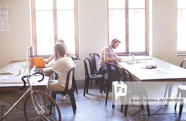 Kreative Geschäftsleute an Tischen im sonnigen Büro