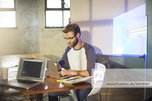Lässiger Geschäftsmann, der eine audiovisuelle Präsentation im Büro vorbereitet.