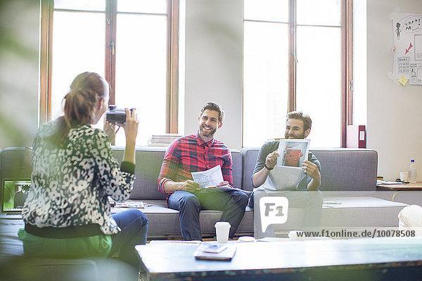 Kreativer Geschäftsmann posiert mit Foto für Mitarbeiter mit Sofortbildkamera im Büro