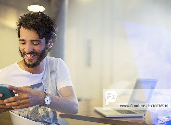 Lächelnder Geschäftsmann SMS mit Handy im Büro
