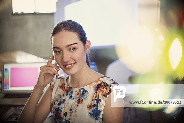 Lächelnde Geschäftsfrau beim Telefonieren im Büro
