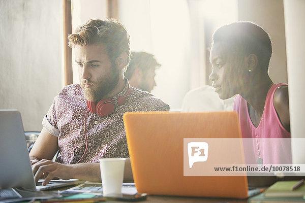 Lässige Geschäftsleute  die an Laptops im Büro arbeiten