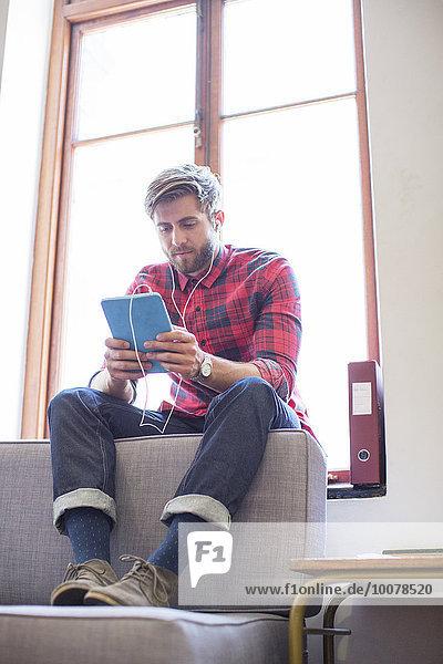 Lässiger Geschäftsmann mit Kopfhörer und digitalem Tablett im Bürofenster