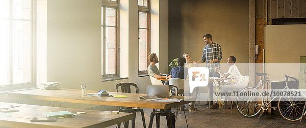 Kreativer Geschäftsmann leitet Meeting am Tisch im Büro