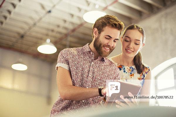 Lässige Geschäftsleute  die sich ein digitales Tablett im Büro teilen
