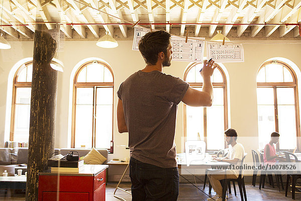 Lässiger Geschäftsmann  der hängende Diagramme im Büro begutachtet.