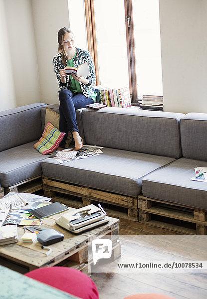 Kreative Geschäftsfrau liest Buch am Fenster im Büro