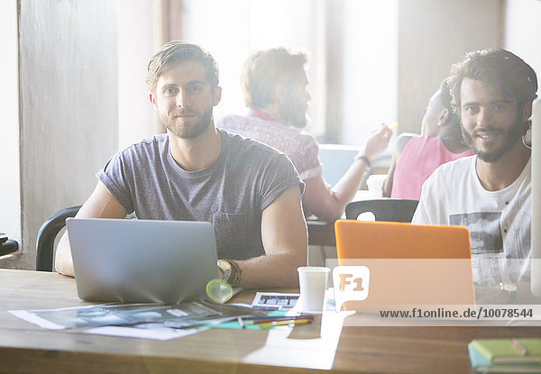 Porträt von kreativen Geschäftsleuten  die an Laptops im Büro arbeiten.