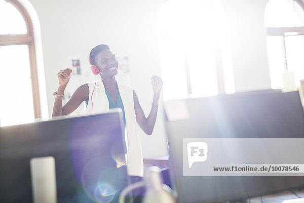 Enthusiastische Geschäftsfrau mit Kopfhörer und Tanz im Büro