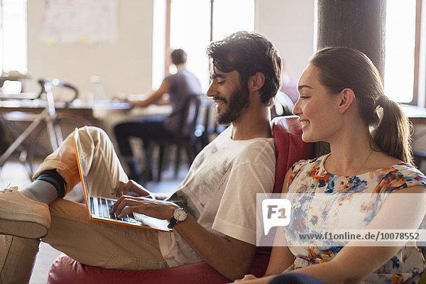 Lässige Geschäftsleute mit Laptop im Büro