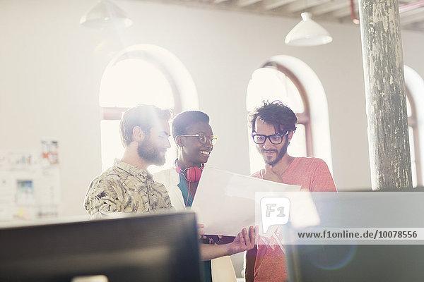 Kreative Geschäftsleute  die den Papierkram in einem sonnigen Büro überprüfen.