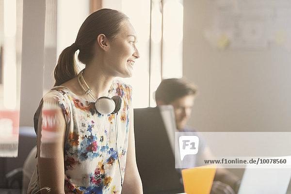 Lächelnde Geschäftsfrau mit Kopfhörer im Büro