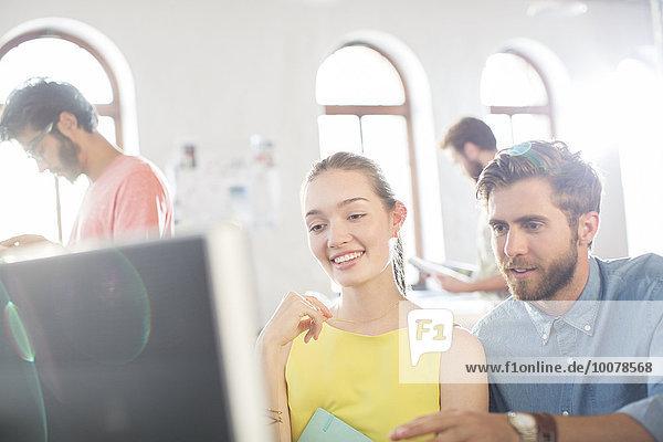 Lässige Geschäftsleute  die den Computer im Büro benutzen