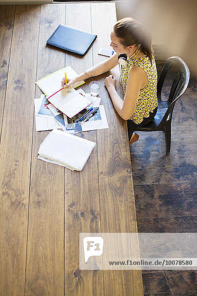 Kreative Geschäftsfrau beim Schreiben im Notebook am Tisch im Büro