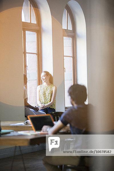 Linsenfackel über lächelnden Geschäftsfrauen im Bürofenster