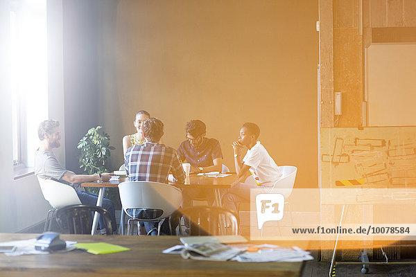 Lens Flare über kreative Geschäftsleute  die sich am Bürotisch treffen