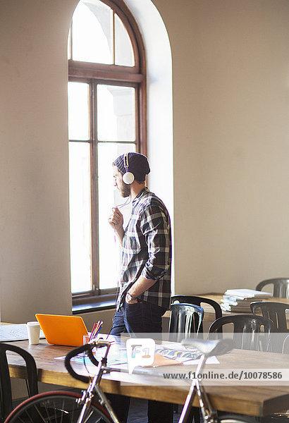 Nachdenklicher kreativer Geschäftsmann mit Kopfhörer  der aus dem Bürofenster schaut