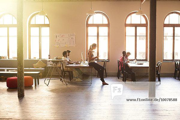 Kreative Geschäftsleute im sonnigen Großraumbüro