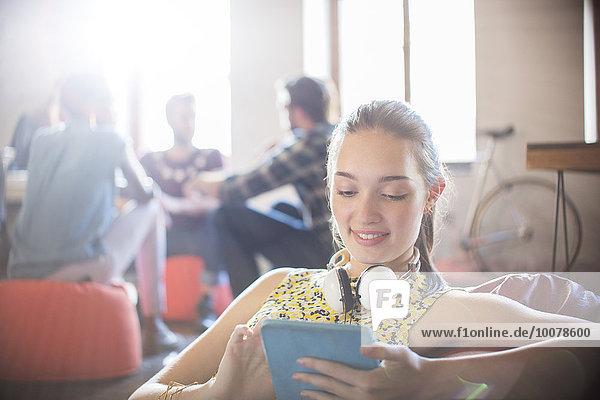 Lässige Geschäftsfrau mit Kopfhörer mit digitalem Tablett im Büro