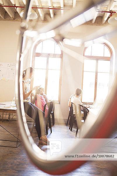 Kreative Geschäftsleute  die im Büro hinter dem Fahrrad arbeiten.