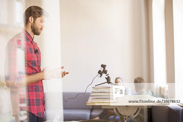 Kreativer Geschäftsmann bei der Videoaufnahme mit dem Handy im Büro