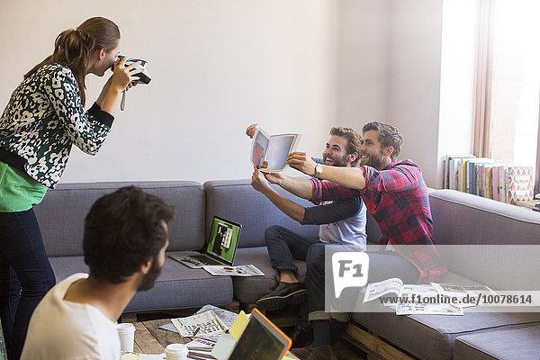 Kreative Geschäftsleute mit Proofs für Mitarbeiter mit Sofortbildkamera