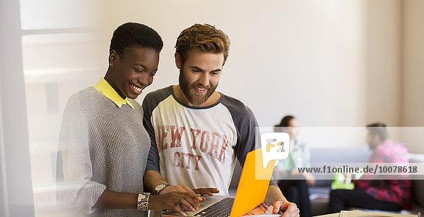 Lässige Geschäftsleute teilen Laptop im Büro