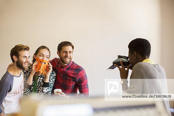 Kreative Geschäftsleute posieren spielerisch für Mitarbeiter mit Sofortbildkamera