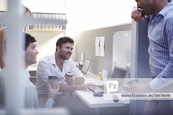 Architekten reden und trinken Kaffee am Laptop im Büro