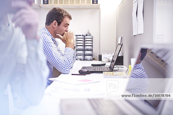 Focused architect using laptop at desk in office