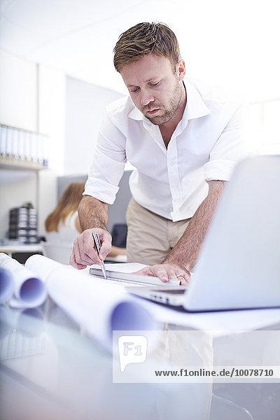 Fokussierter Architekt bei der Erstellung von Bauplänen im Büro