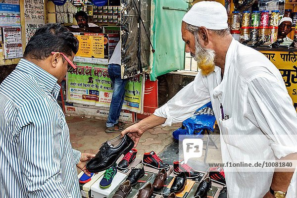 India  Asian  Mumbai  Dharavi  Shahu Nagar Road  slum  low income  poor  poverty  man  working  Muslim  men´s  shoes  sale  selling  customer  buying  sidewalk vendor.