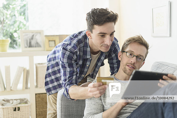 Caucasian gay couple shopping online on digital tablet