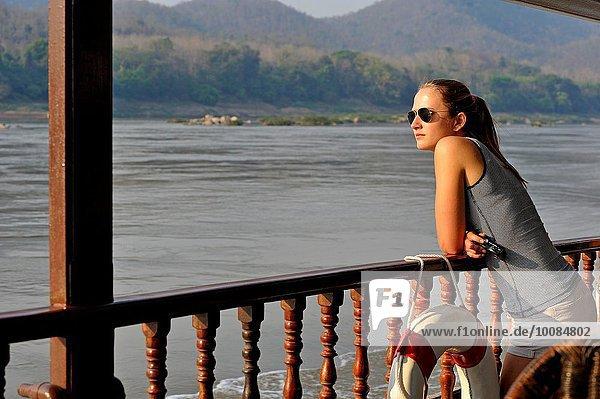 zwischen inmitten mitten stehend junge Frau junge Frauen Boot Lodge Landhaus Geländer Kreuzfahrtschiff Südostasien