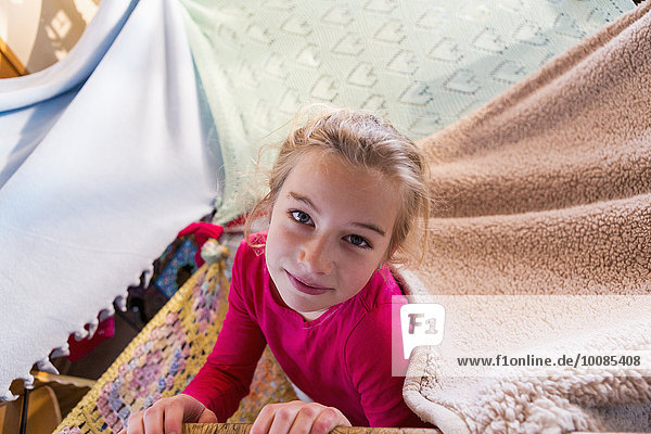 Caucasian girl playing in blanket fort