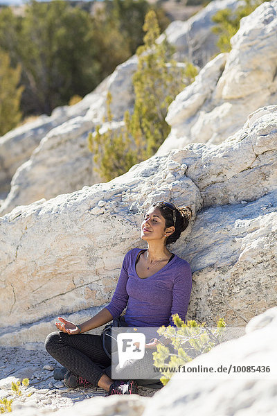 Hispanic woman meditating on rocky hillside