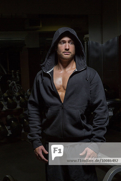 Caucasian athlete wearing hoody at night