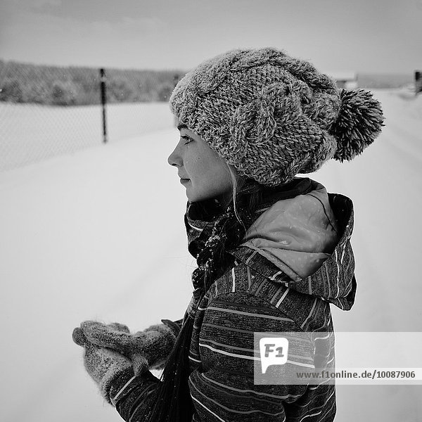 Caucasian girl wearing knit cap and gloves in snow