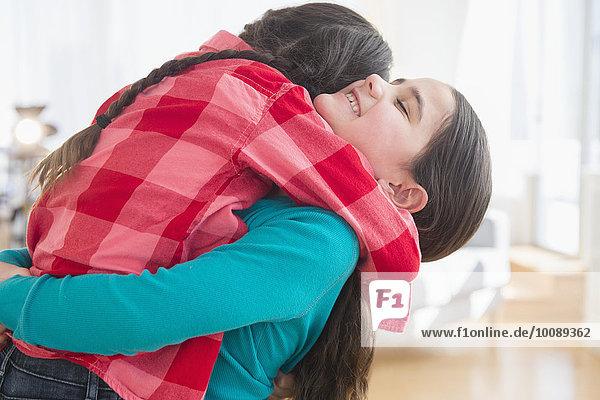 Close up of Caucasian sisters hugging