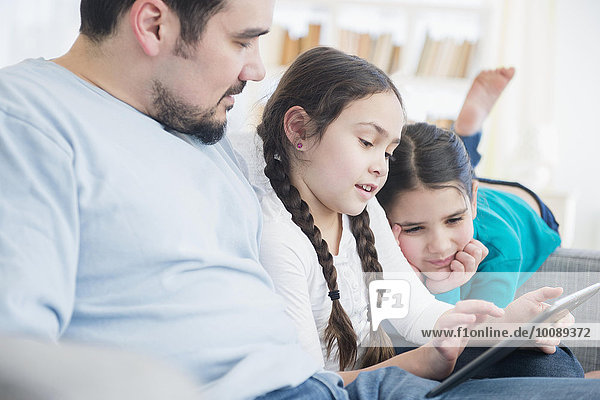 Caucasian father and daughters using digital tablet on sofa